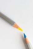 Crayons bleus et jaunes sur un blanc Images stock