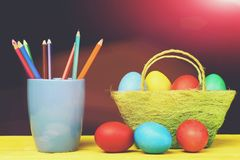Crayons in blue mug and painted eggs in green basket. Happy easter holidays egg Crayons in blue mug and painted eggs in green cloth basket for Easter on yellow Royalty Free Stock Image