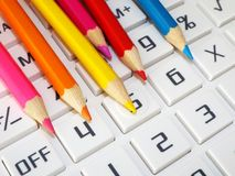 Crayons bring color. Colored pencils jut on the keypad of a calculator Royalty Free Stock Images