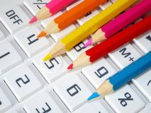 Crayons bring color. Colored pencils jut on the keypad of a calculator Royalty Free Stock Photos