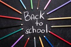 Crayons colorés autour de nouveau aux mots d'école sur le fond de noir d'ardoise De nouveau au concept d'école Vue supérieure image stock