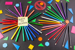 Crayons colorés aux cercles et au titre de nouveau à l'école écrite sur le morceau de papier sur le tableau Photo stock