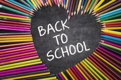 Crayons colorés avec de nouveau au mot d'école Images stock