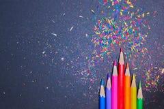 Crayons colorés avec les copeaux colorés sur un fond noir Photo stock