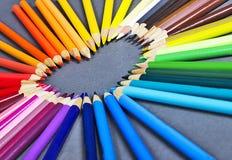 Crayons colorés brillamment en bois s'étendant sur un fond gris sous forme de coeur Photographie stock