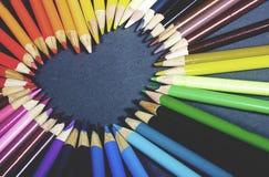 Crayons colorés brillamment en bois s'étendant sur un fond gris sous forme de coeur Image libre de droits