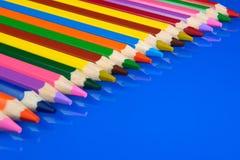 Crayons colorés d'isolement sur le fond bleu avec la réflexion Images libres de droits