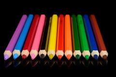 Crayons colorés d'isolement sur le fond noir avec la réflexion Images libres de droits