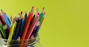 Crayons colorés dans le pot en verre tournant sur le fond jaune avec l'espace de copie Boucle sans couture clips vidéos