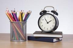 Crayons colorés dans le réveil se tenant prêt de support Image stock