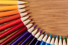 Crayons colorés dans un modèle semi-circulaire sur une table en bambou a image stock