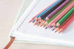 Crayons colorés de crayon de plan rapproché sur le carnet de notes à spirale et le vert pas Image stock