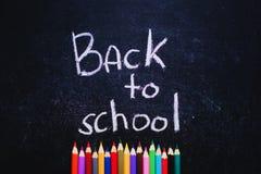 Crayons colorés dessous de nouveau aux mots d'école sur le fond de noir d'ardoise De nouveau au concept d'école Vue supérieure photo stock