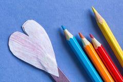 Crayons colorés et papier entendus sur le fond de papier bleu Images libres de droits