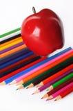 Crayons colorés et une pomme sur un fond blanc Photos libres de droits