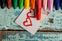Crayons colorés lumineux sur un vieux fond en bois de vert bleu Deux coeurs rouges peints sur une tranche de papier Photo stock