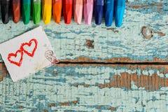 Crayons colorés lumineux sur un vieux fond en bois de vert bleu Deux coeurs rouges peints sur une tranche de papier Photos stock