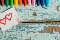 Crayons colorés lumineux sur un vieux fond en bois de vert bleu Deux coeurs rouges peints sur une tranche de papier Photographie stock libre de droits