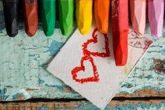 Crayons colorés lumineux sur un vieux fond en bois de vert bleu Deux coeurs rouges peints sur une tranche de papier Photographie stock