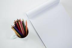 Crayons colorés maintenus dans la tasse avec le bloc-notes Photos libres de droits