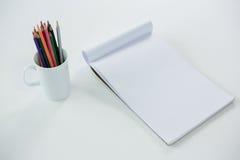 Crayons colorés maintenus dans la tasse avec le bloc-notes Photographie stock