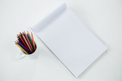 Crayons colorés maintenus dans la tasse avec le bloc-notes Photo stock