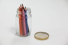 Crayons colorés maintenus dans un pot en verre Photos stock