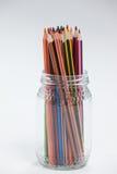 Crayons colorés maintenus dans un pot en verre Images libres de droits