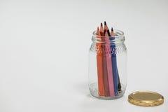 Crayons colorés maintenus dans un pot en verre Photographie stock