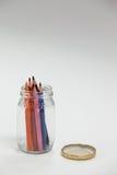 Crayons colorés maintenus dans un pot en verre Image libre de droits