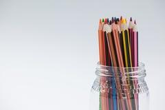 Crayons colorés maintenus dans un pot en verre Photo libre de droits