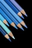 8 crayons colorés par bleu - fond noir Image libre de droits