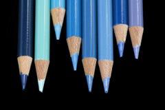 8 crayons colorés par bleu - fond noir Images libres de droits