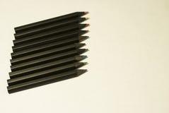 Crayons colorés par noir sur le fond blanc Image libre de droits