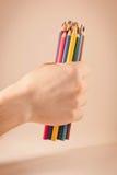 Crayons colorés par participation de main Photos stock