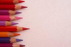 Crayons colorés par rouge au-dessus d'un fond rose image stock