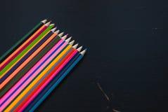 Crayons colorés réglés sur le fond en bois noir, Photos libres de droits