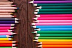 Crayons colorés sur le fond brun se situant dans les bords opposés de la table en bois Photos libres de droits