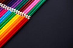 Crayons colorés sur le fond foncé se situant dans les coins opposés Photographie stock