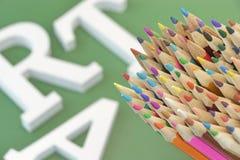 Crayons colorés sur le fond vert avec Art Sign brouillé Image libre de droits