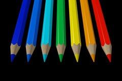 Crayons colorés sur le noir Photos stock