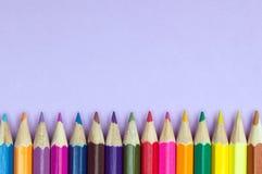 Crayons colorés sur un fond lilas Photographie stock libre de droits