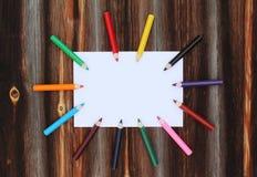 Crayons colorés sur une bonne feuille de papier sur le vieux fond en bois Images libres de droits