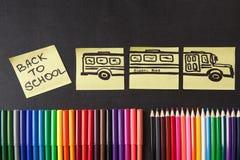 Crayons colorés, titres de nouveau à l'école et autobus scolaire dessiné sur les morceaux de papier sur le tableau Photo libre de droits