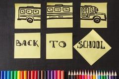 Crayons colorés, titres de nouveau à l'école et autobus scolaire dessiné sur les morceaux de papier sur le tableau Photos stock