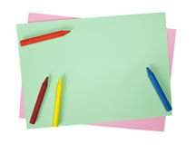 Crayons on colored papers Stock Images