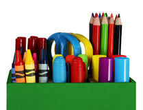 Crayons, colored pencils and pens. Colorful crayons, colored pencils, markers, pens and scissors in a green box on a desk royalty free stock image
