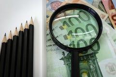 Crayons comme se lèvent graphique et loupe sur d'euro billets de banque Image libre de droits