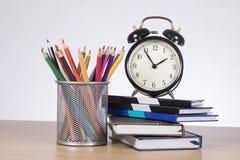 Crayons dans le récipient avec le réveil sur des livres Image libre de droits