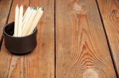 Crayons dans une tasse sur une table en bois Photos libres de droits